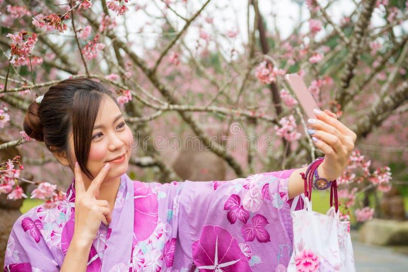 Ragazza asiatica che prende la foto del selfie al parco di sakura immagine stock