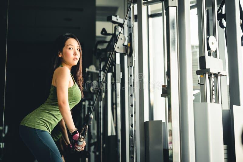 Ragazza asiatica che si esercita alla palestra, preparantesi sulla macchina del cavo di pushdown, con lo spazio della copia Stile immagine stock