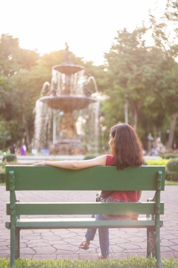 Ragazza asiatica che si siede sul banco nel parco immagine stock
