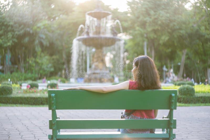 Ragazza asiatica che si siede sul banco nel tono d'annata s del parco fotografia stock