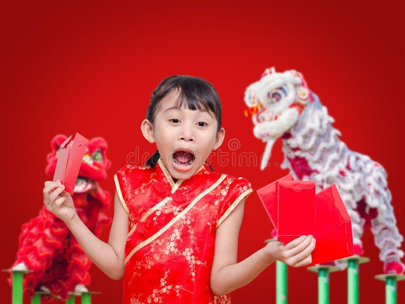 Ragazza asiatica che tiene i soldi rossi del pacchetto fotografia stock libera da diritti
