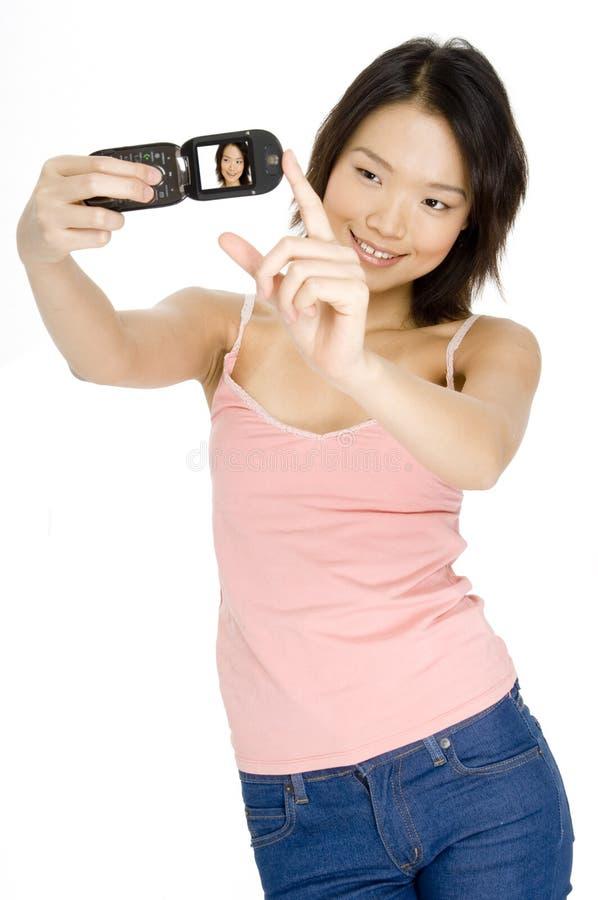 Ragazza asiatica con Cameraphone immagini stock libere da diritti