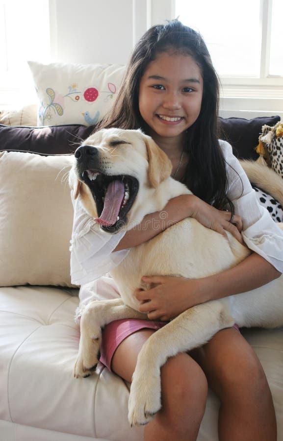 Ragazza asiatica con il suo cane di sbadiglio fotografia stock libera da diritti