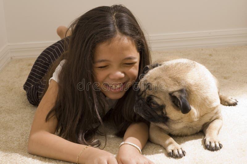 Ragazza asiatica con il suo Pug dell'animale domestico immagine stock libera da diritti