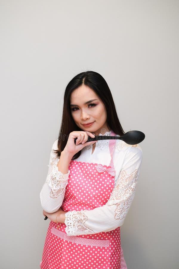 Ragazza asiatica con l'attrezzatura piacevole, indossante un grembiule lungo del pois fotografia stock libera da diritti