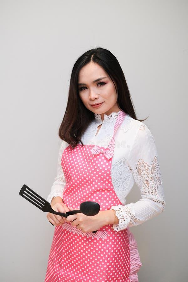 Ragazza asiatica con l'attrezzatura piacevole, indossante un grembiule lungo del pois fotografia stock