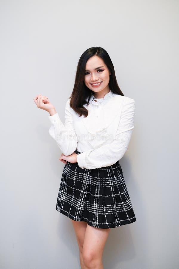Ragazza asiatica con l'attrezzatura piacevole, la minigonna e la camicia lunga della manica immagini stock libere da diritti