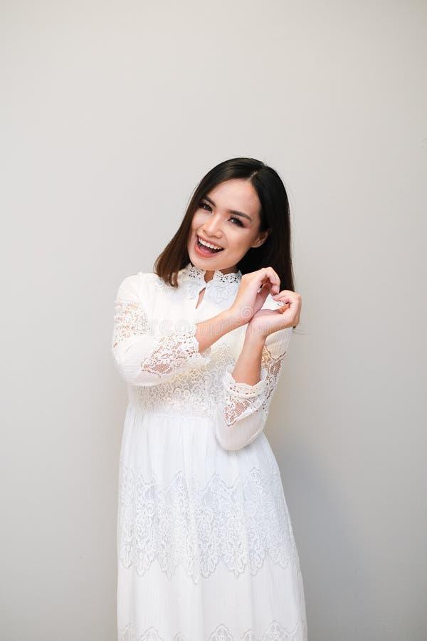 Ragazza asiatica con l'attrezzatura piacevole, portante un vestito lungo dal pizzo fotografia stock
