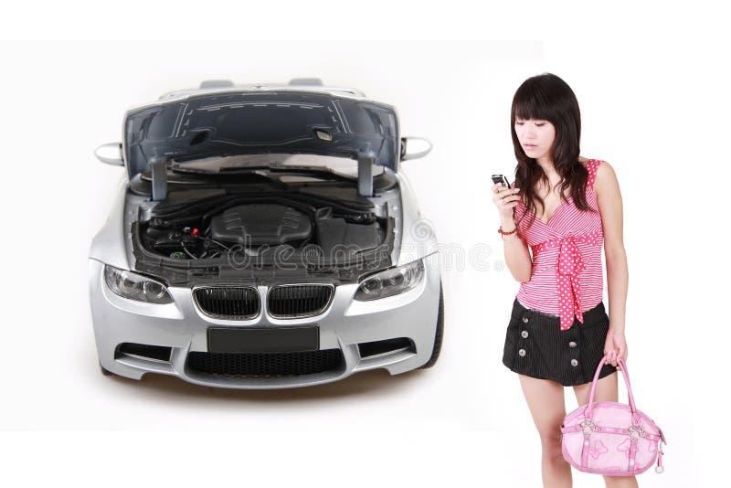 Ragazza asiatica con l'automobile di ripartizione. fotografia stock