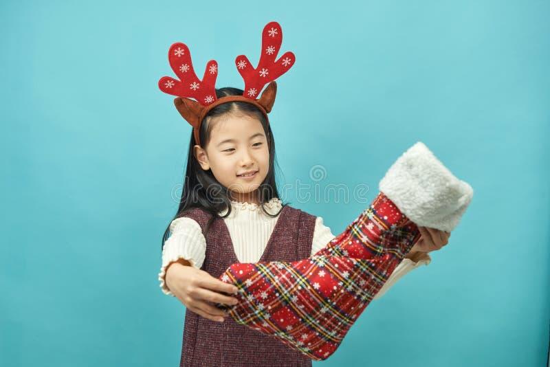 Ragazza asiatica con un bambino del copricapo di concetto di Natale immagini stock libere da diritti