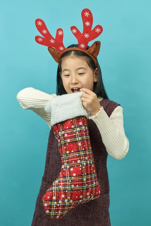 Ragazza asiatica con un bambino del copricapo di concetto di Natale fotografie stock libere da diritti