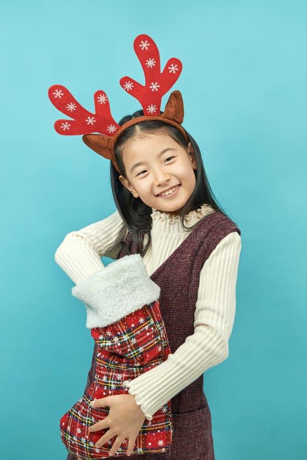 Ragazza asiatica con un bambino del copricapo di concetto di Natale fotografia stock