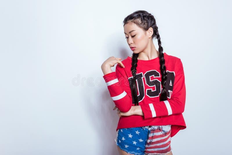 Ragazza asiatica dei pantaloni a vita bassa alla moda sensuali in attrezzatura patriottica americana isolata su grey fotografie stock libere da diritti