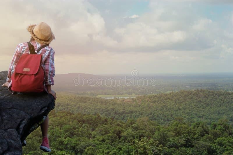 Ragazza asiatica dei pantaloni a vita bassa con lo zaino che gode del tramonto sulla montagna di punta Concetto di avventura di s fotografie stock