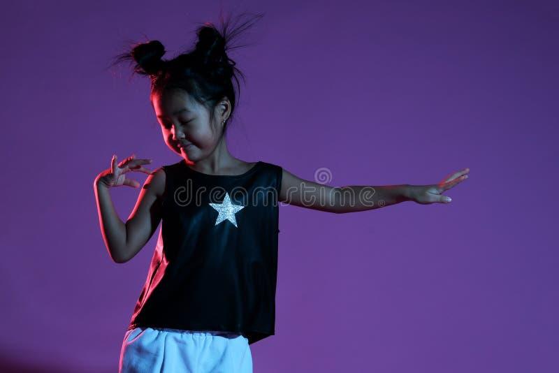 Ragazza asiatica del bambino in camicia e pantaloni con le stelle ed i balli fotografie stock