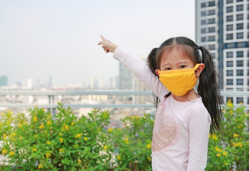 Ragazza asiatica del bambino che indossa una maschera di protezione contro il PM 2 inquinamento atmosferico 5 con indicare su nel immagini stock