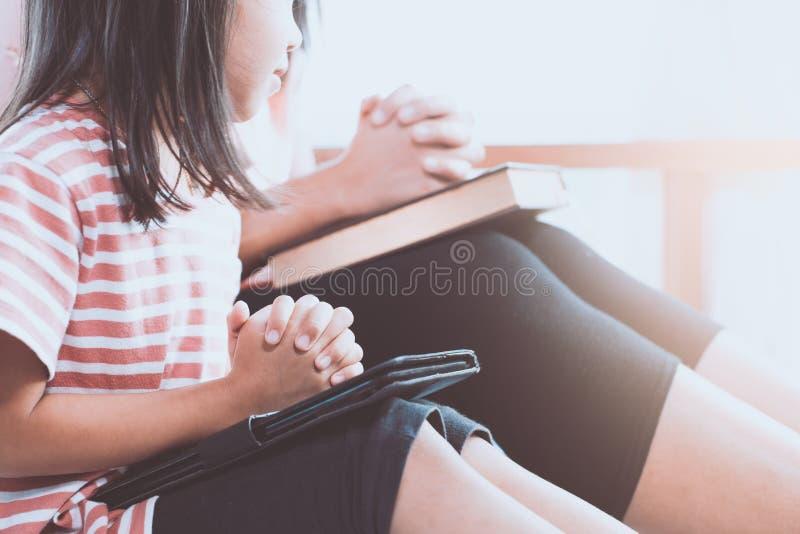 Ragazza asiatica del piccolo bambino e sua la madre che pregano con la mano piegata fotografia stock libera da diritti