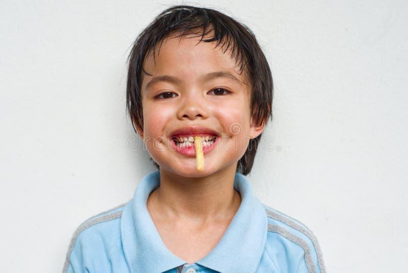 Ragazza asiatica del ritratto che mangia la patata fritta con il fronte divertente fotografia stock libera da diritti