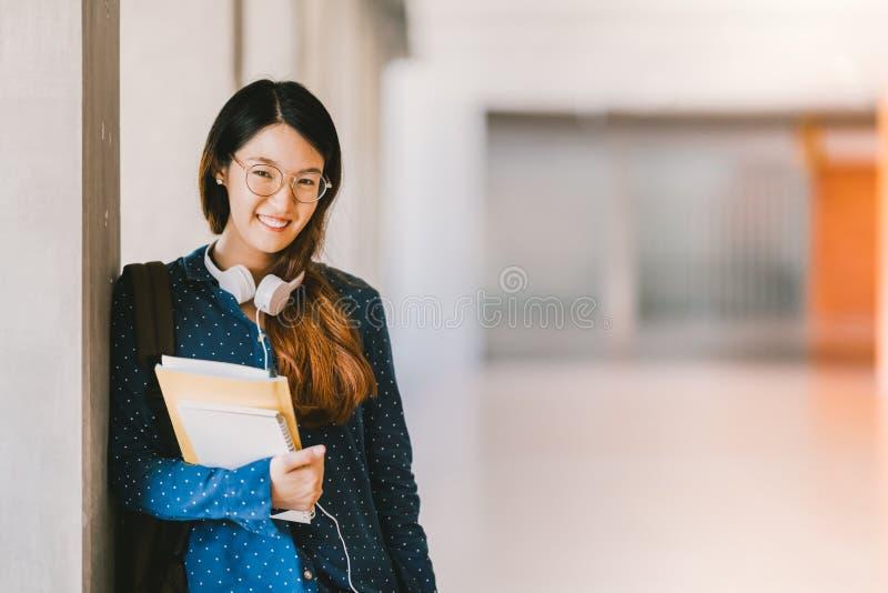 Ragazza asiatica della High School o occhiali d'uso dello studente di college, sorridenti nel campus universitario con lo spazio  immagini stock