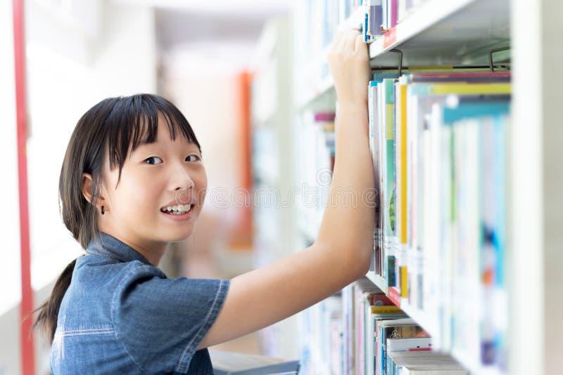 Ragazza asiatica dello studente nella stanza delle biblioteche fotografia stock libera da diritti