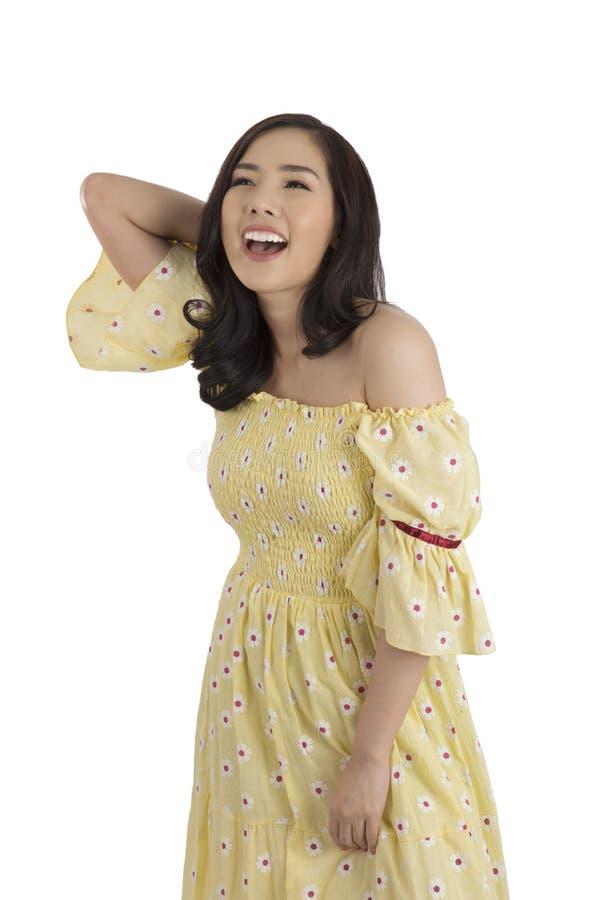 Ragazza asiatica di bellezza che porta vestito floreale giallo che posa nello studio fotografia stock libera da diritti