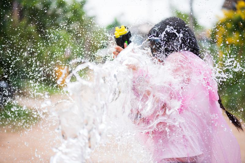 Ragazza asiatica di giovane bellezza felice con la camicia d'uso di estate della pistola a acqua nel festival di Songkran - festi fotografie stock