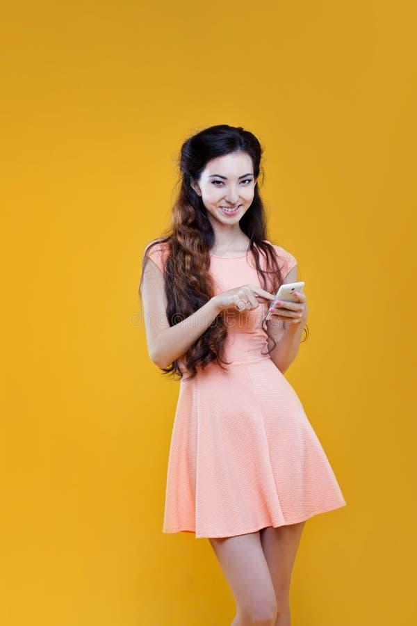 Ragazza asiatica di modo con il telefono cellulare Ritratto su fondo giallo fotografie stock libere da diritti