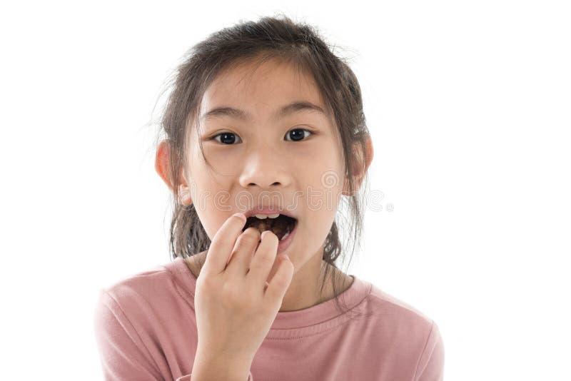 Ragazza asiatica felice che mangia i fiocchi di granturco del cioccolato immagini stock libere da diritti