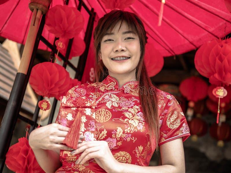 Ragazza asiatica felice che tiene busta rossa per arrendersi festival cinese del nuovo anno Nuovo anno cinese fotografie stock