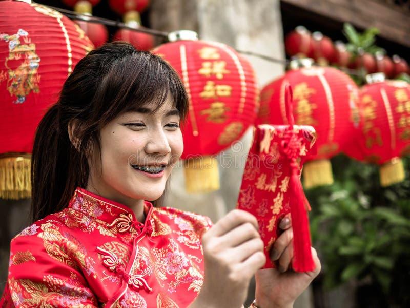 Ragazza asiatica felice che tiene busta rossa per arrendersi festival cinese del nuovo anno Nuovo anno cinese fotografia stock