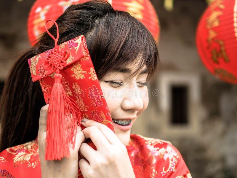 Ragazza asiatica felice che tiene busta rossa per arrendersi festival cinese del nuovo anno Nuovo anno cinese immagini stock