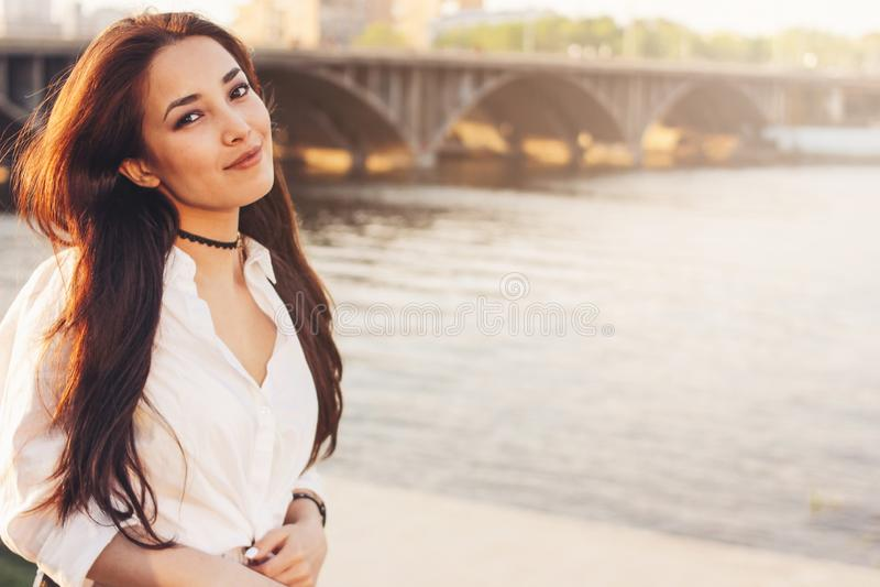 Ragazza asiatica felice dei bei capelli lunghi positivi in camicia bianca sul fondo del ponte del fiume della citt?, tempo di vac immagine stock libera da diritti