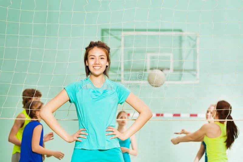 Ragazza asiatica felice, membro del team di pallavolo, in palestra immagini stock libere da diritti
