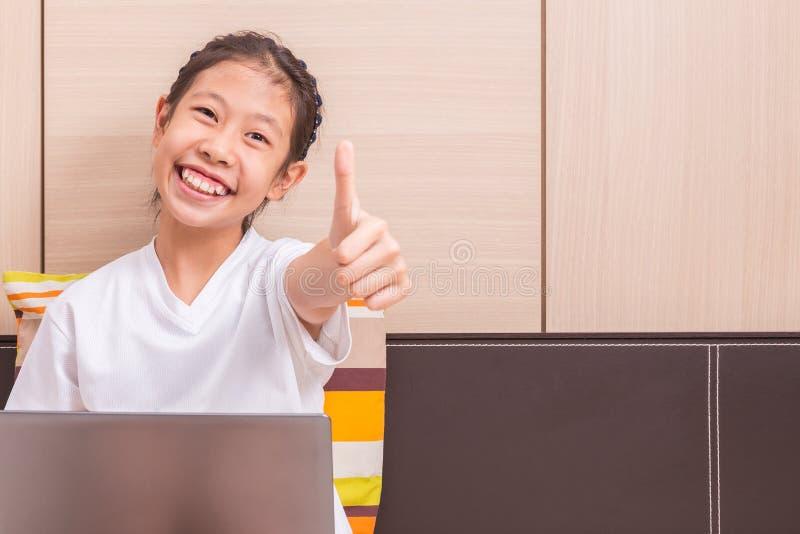 Ragazza asiatica sorridente felice che per mezzo del computer portatile per studiare in lei fotografia stock libera da diritti