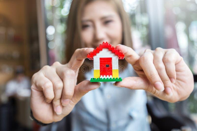 Ragazza asiatica sveglia che mostra il modello rosso della casa del tetto immagini stock libere da diritti