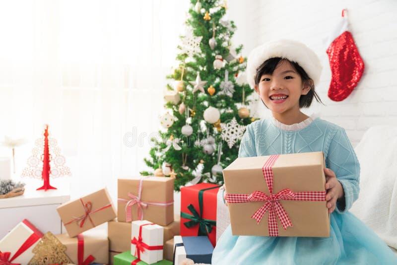Ragazza asiatica sveglia che tiene un contenitore di regalo di Natale fotografia stock libera da diritti