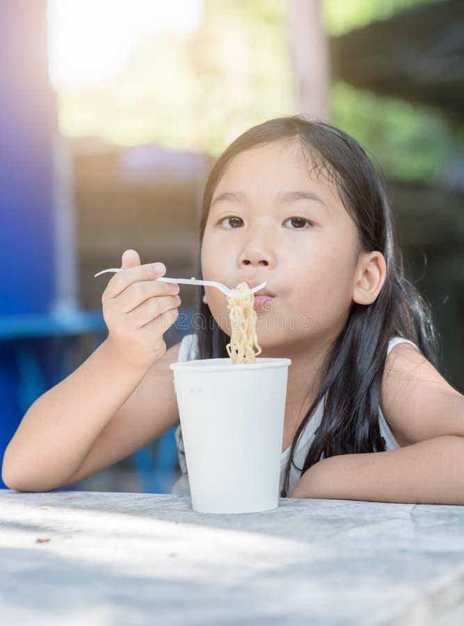 Ragazza asiatica sveglia del bambino che mangia la tazza della tagliatella del instand, fotografia stock libera da diritti