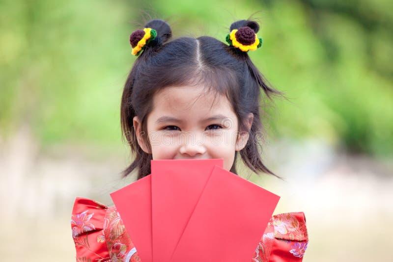 Ragazza asiatica sveglia del bambino che tiene busta rossa fotografie stock libere da diritti