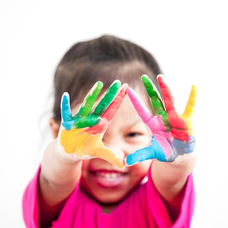 Ragazza asiatica sveglia del bambino con le mani dipinte in pittura variopinta immagine stock libera da diritti