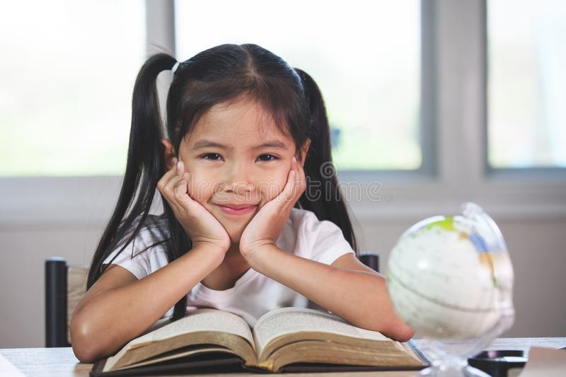 Ragazza asiatica sveglia del bambino con un libro che sorride nell'aula fotografia stock libera da diritti