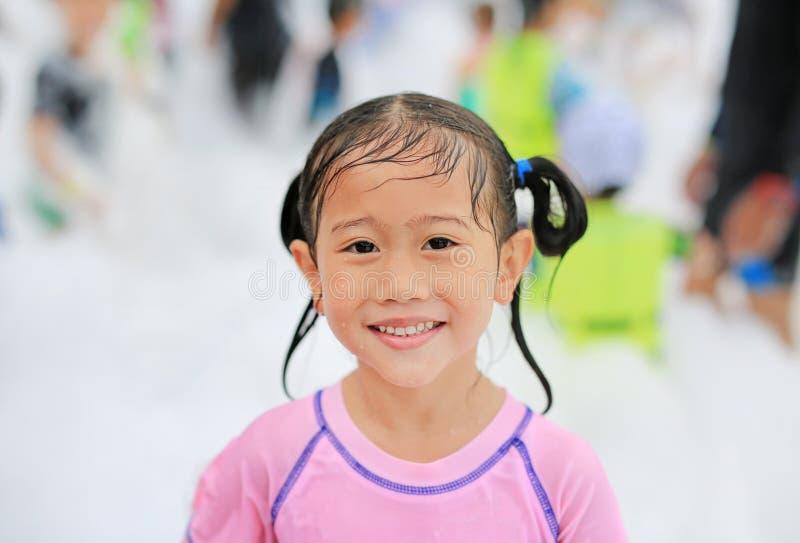 Ragazza asiatica sveglia del bambino del primo piano piccola che sorride divertendosi nel partito della schiuma allo stagno all'a immagini stock