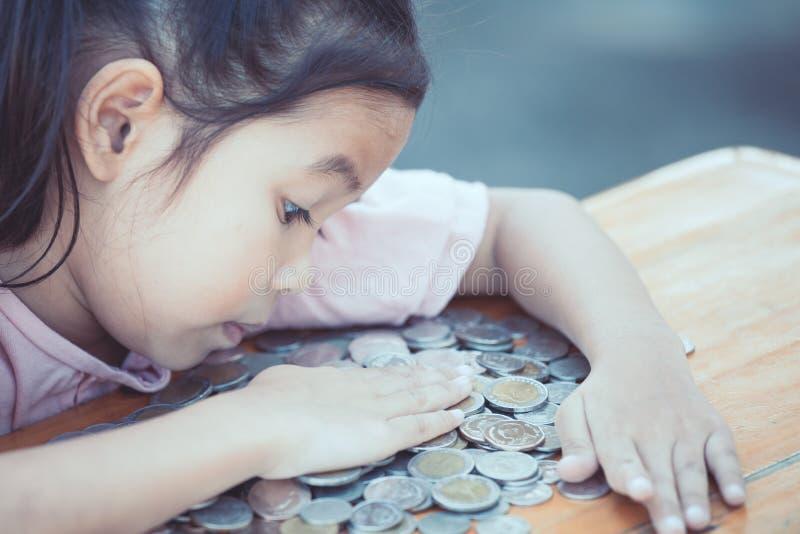 Ragazza asiatica sveglia del piccolo bambino che abbraccia e avara i suoi soldi immagini stock libere da diritti