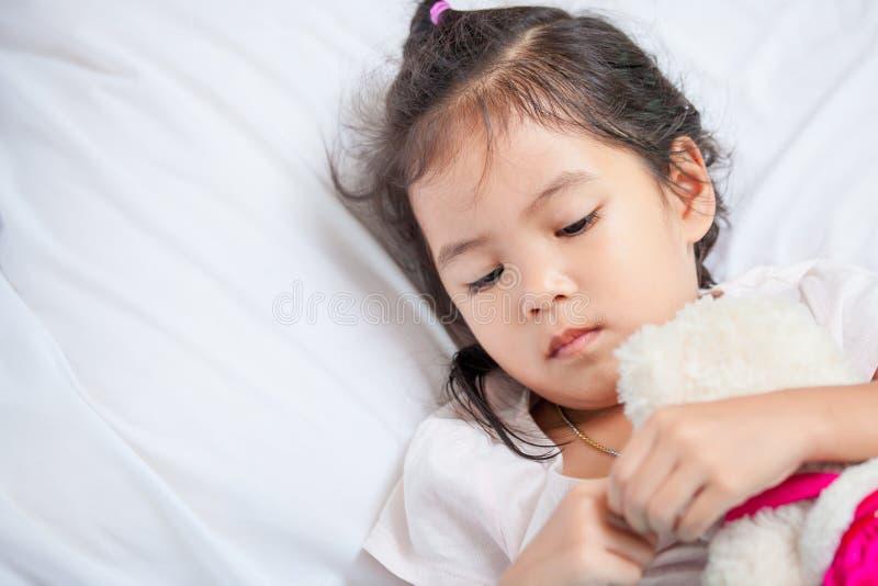 Ragazza asiatica sveglia del piccolo bambino che abbraccia il suo orsacchiotto immagine stock