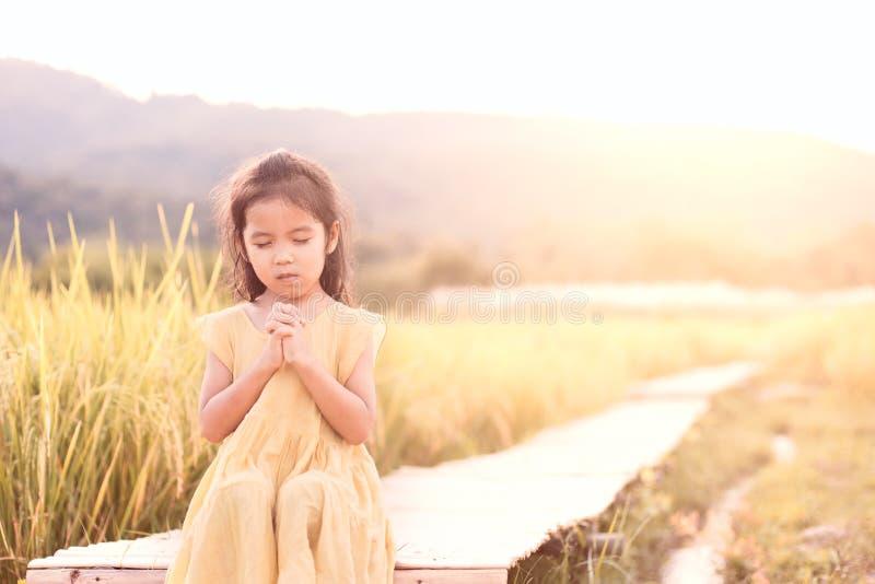 Ragazza asiatica sveglia del piccolo bambino che prega con piegato la sua mano fotografie stock libere da diritti