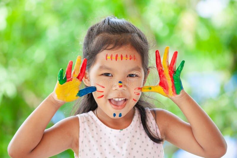 Ragazza asiatica sveglia del piccolo bambino con sorridere dipinto delle mani immagine stock libera da diritti
