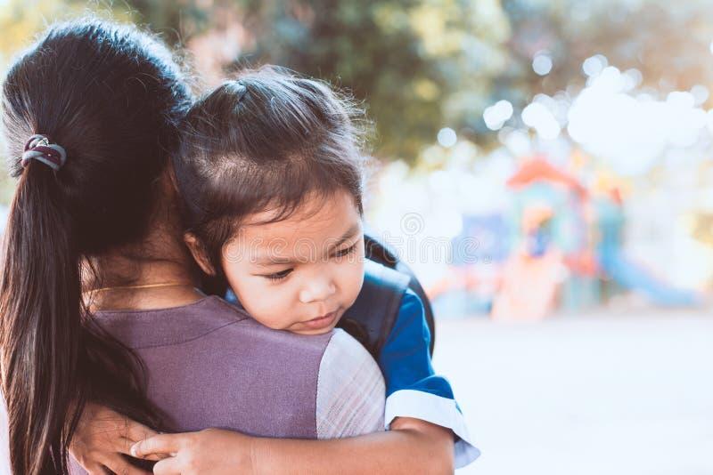 Ragazza asiatica sveglia dell'allievo con lo zaino che abbraccia sua madre fotografia stock