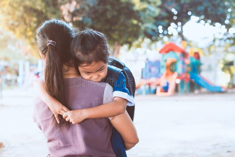 Ragazza asiatica sveglia dell'allievo con lo zaino che abbraccia sua madre immagine stock