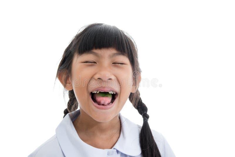 Ragazza asiatica sveglia in uniforme le che mostra i denti rotti fotografia stock