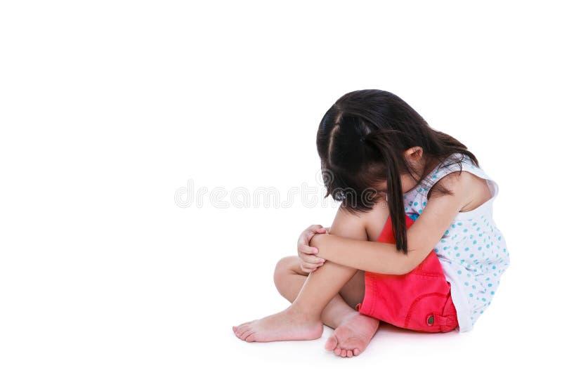 Ragazza asiatica triste che si siede a piedi nudi sul pavimento con lo spazio della copia Isolat fotografia stock