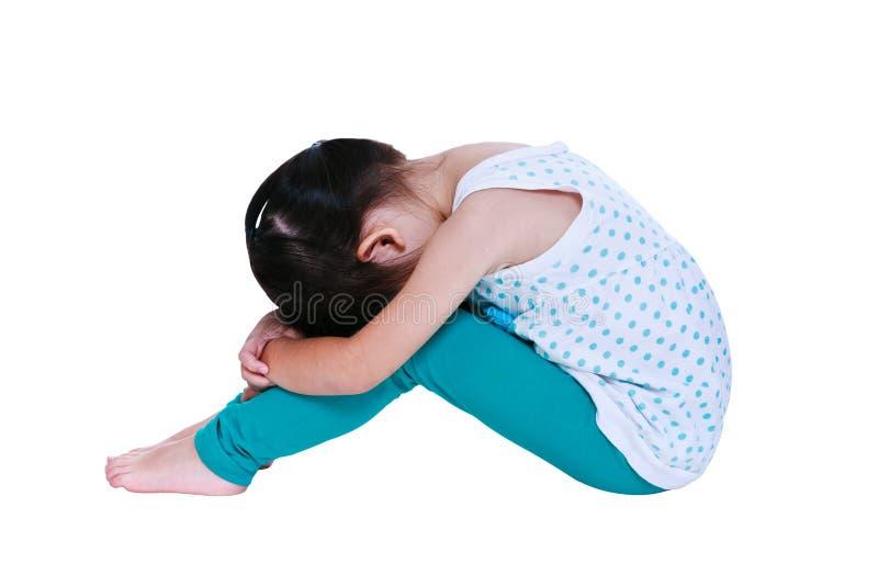 Ragazza asiatica triste che si siede a piedi nudi sul pavimento Isolato sulla parte posteriore di bianco fotografia stock libera da diritti